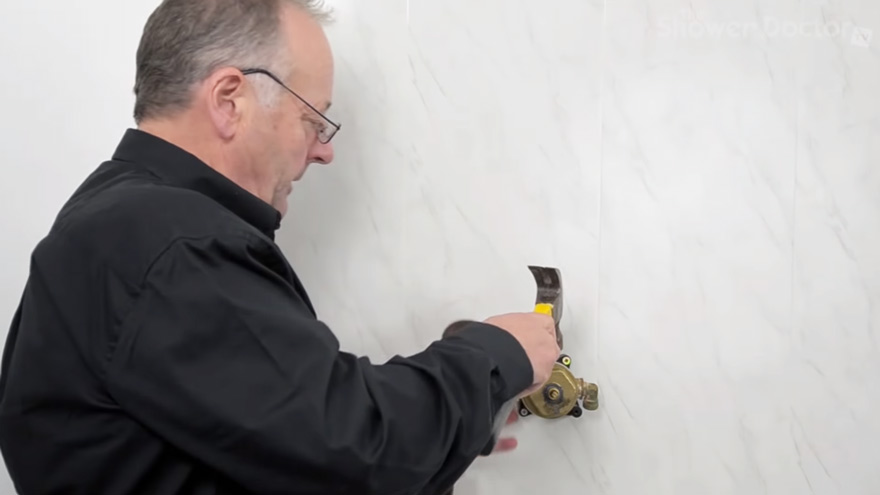 Using hammer to loosen the brass nut.